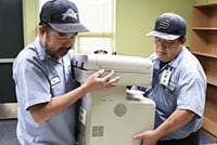 Two Fresno Unified staff employees lift and carry a printer.